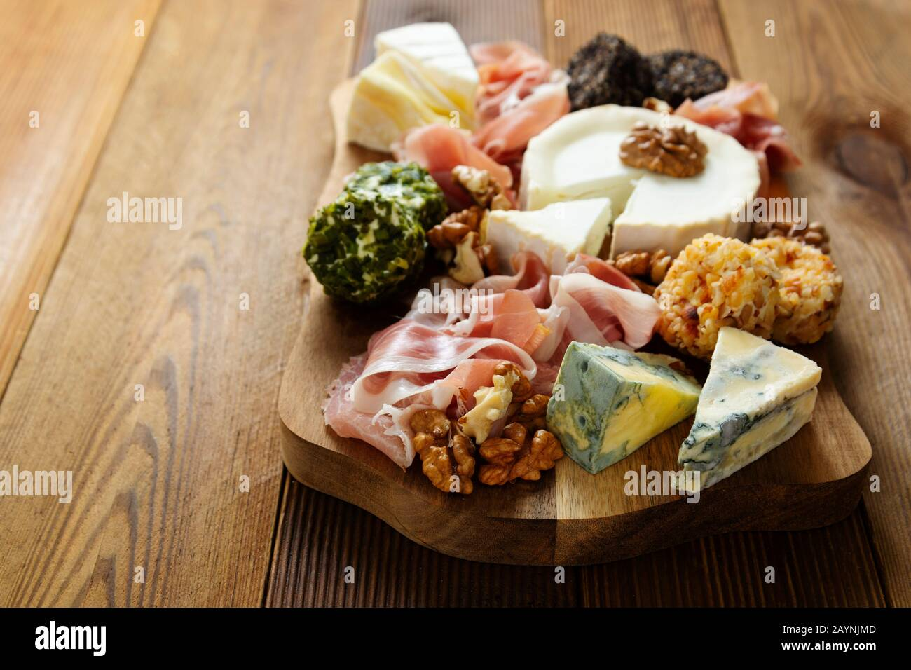 Cheese plate, various types of cheeses, grapes, walnuts and honey and prosciutto. Wooden cutting board. Stock Photo
