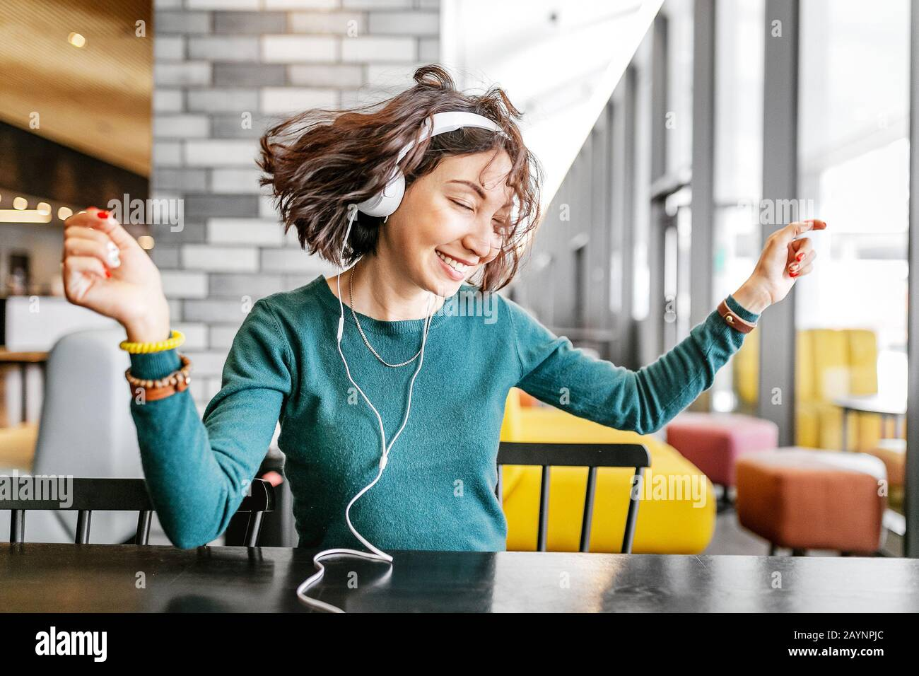Young happy woman wearing headphones listening to her favorite song by wi-fi internet Stock Photo