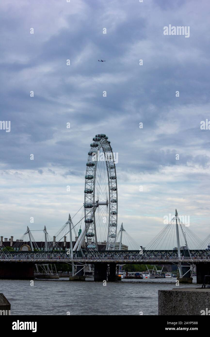London/ England - may 24 2019: A portrait of the London eye with a moody sky and an airplane above it and a bridge over the Thames. Stock Photo