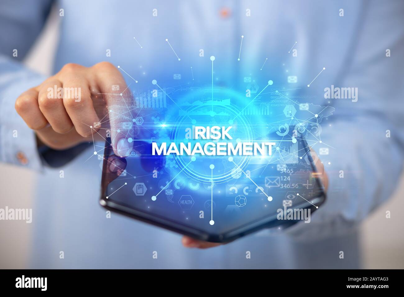 Businessman holding a foldable smartphone with RISK MANAGEMENT inscription, new business concept Stock Photo