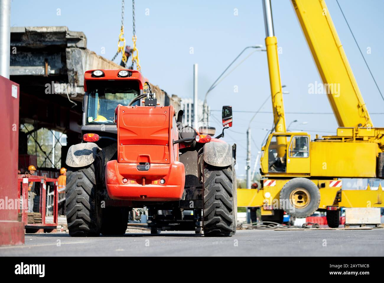 Constuction site heavy machinery industrial background. Telescopic handler vehicle and big mobile crane working at city building development Stock Photo