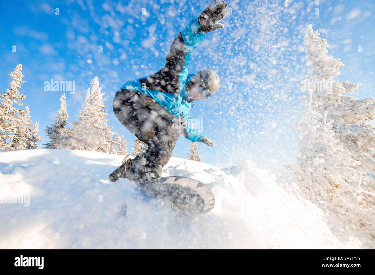 Active man snowboarder riding on slope during sunny day in mountains. Dust snow forest Stock Photo