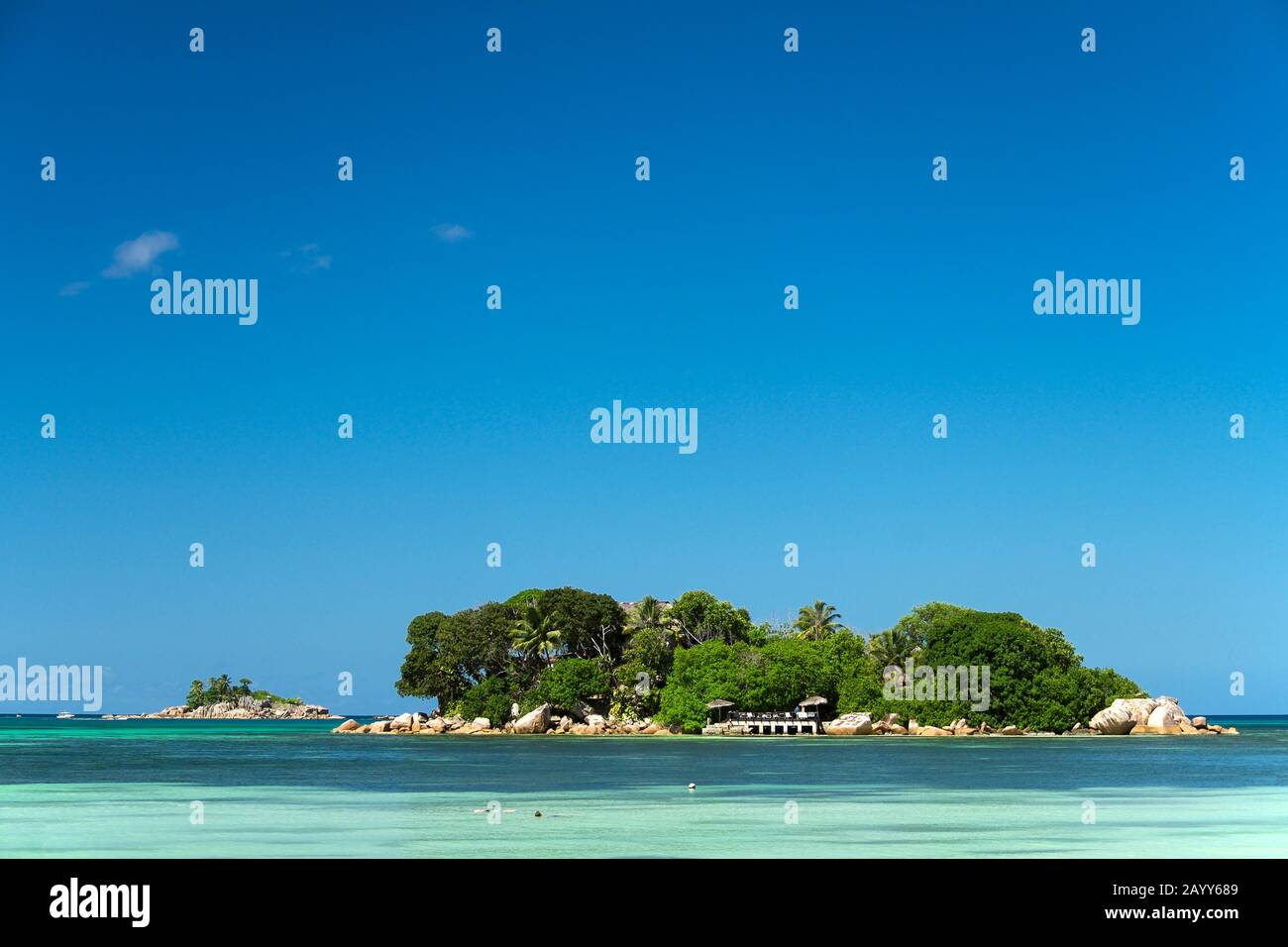 Snorkelers in tropical clerar waters by Chauve Souris Island with St Pierre Islet in the background. Praslin Island, Seychelles Stock Photo