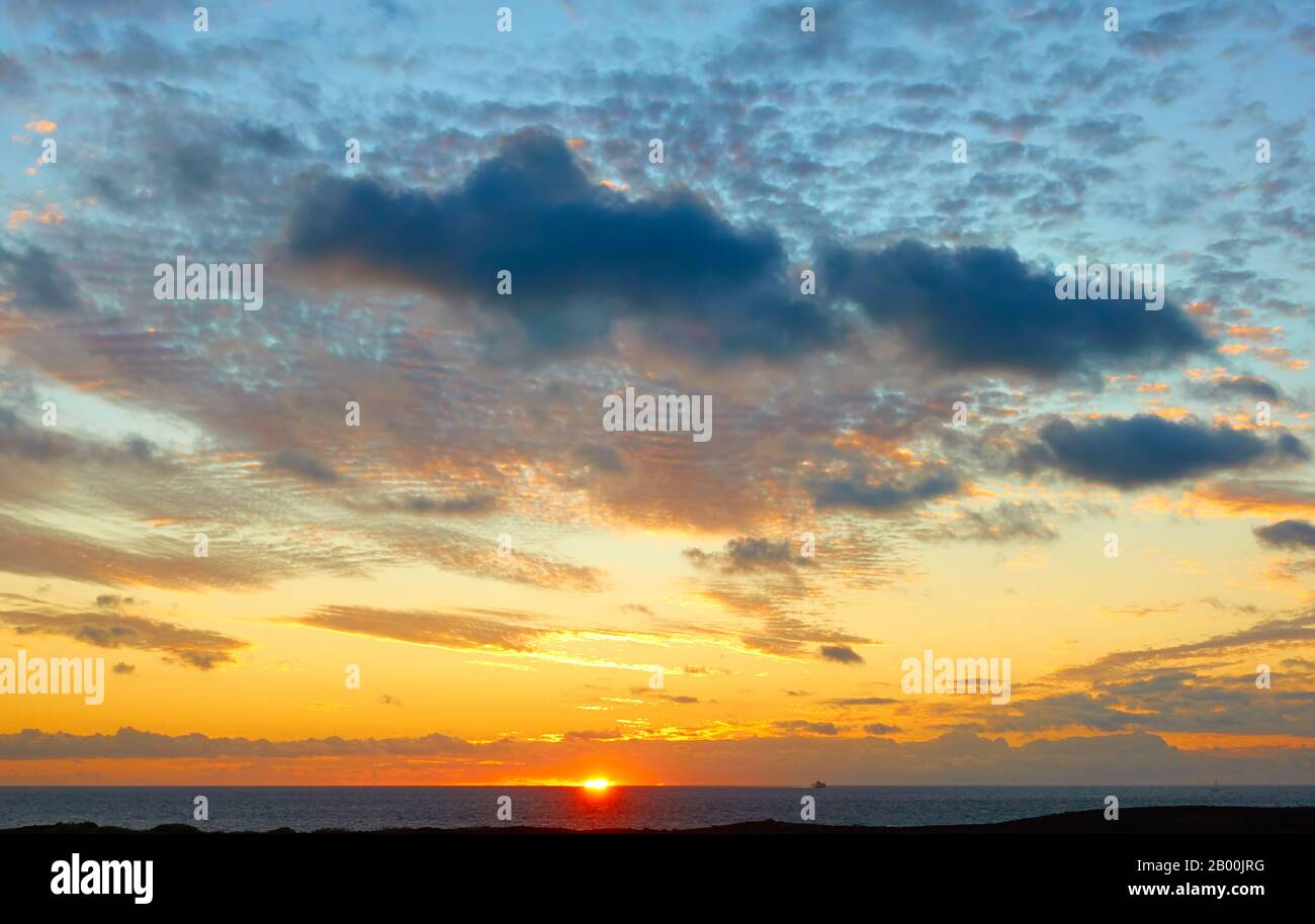 The sun is about to go under sea horizon.  Sunset landscape - seascape, background with space for your own text Stock Photo
