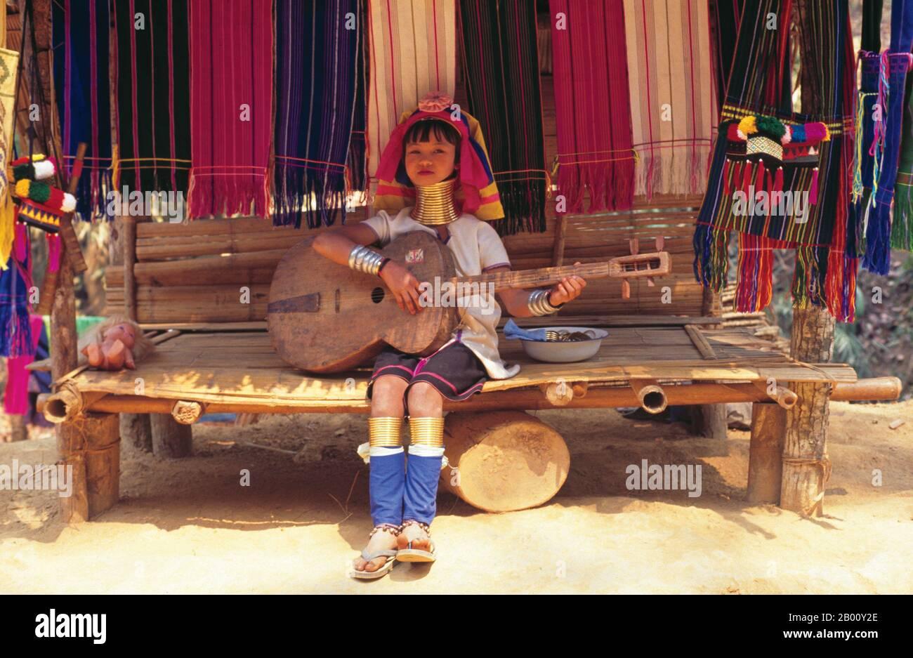 Thailand: Padaung (Long Neck Karen) playing a homemade guitar, village near Mae Hong Son.  The Padaung or Kayan Lahwi or Long Necked Karen are a subgroup of the Kayan, a mix of Lawi tribe , Kayan tribe and several other tribes. Kayan are a subgroup Red Karen (Karenni) people, a Tibeto-Burman ethnic minority of Burma (Myanmar). Stock Photo