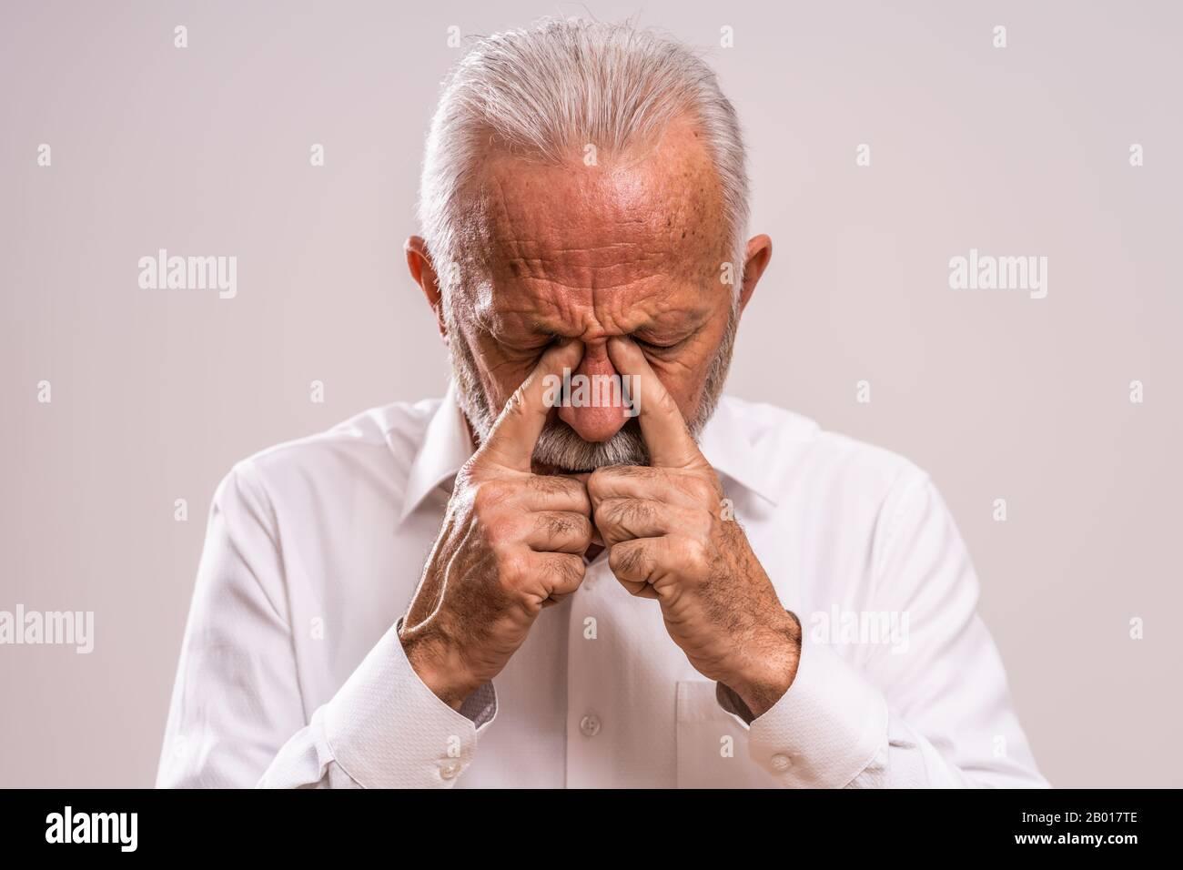 Portrait of senior man who is having pain in sinus. Stock Photo