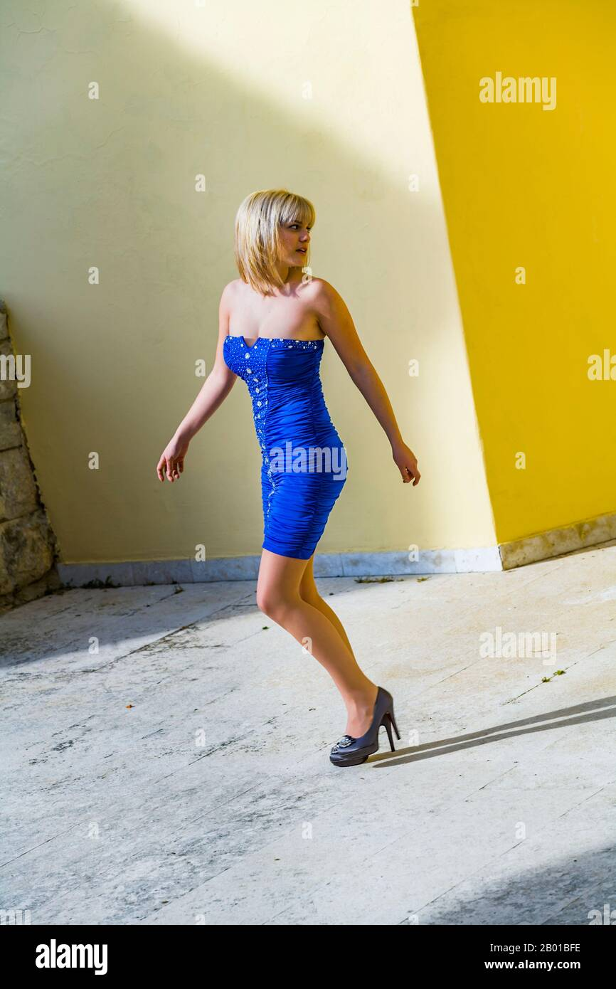 Teen girl aka young woman legs heels walking alone on street looking back over shoulder daylight sunshine sunlight suspicious suspicion Stock Photo