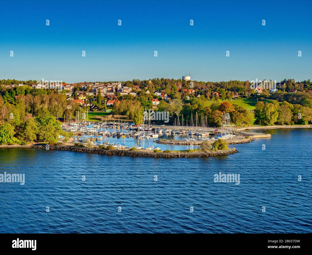 A view of the island of Lidingo, Stockholm, Sweden, from the water, with houses in a green landscape and a marina, an example of the Swedish lifestyle Stock Photo