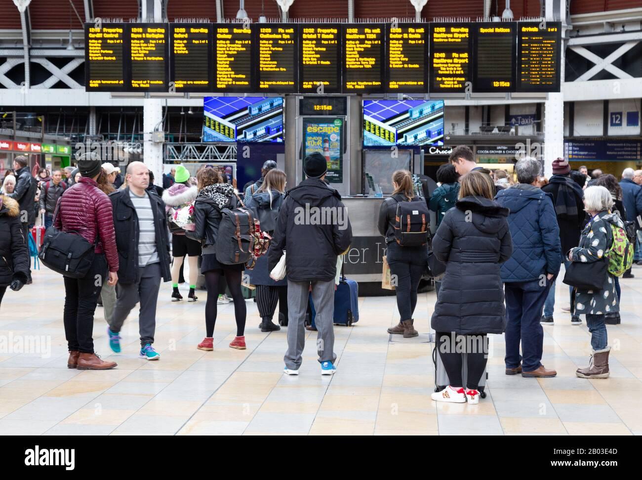 Train passengers looking at the departure board, Paddington train Station, Paddington London UK Stock Photo