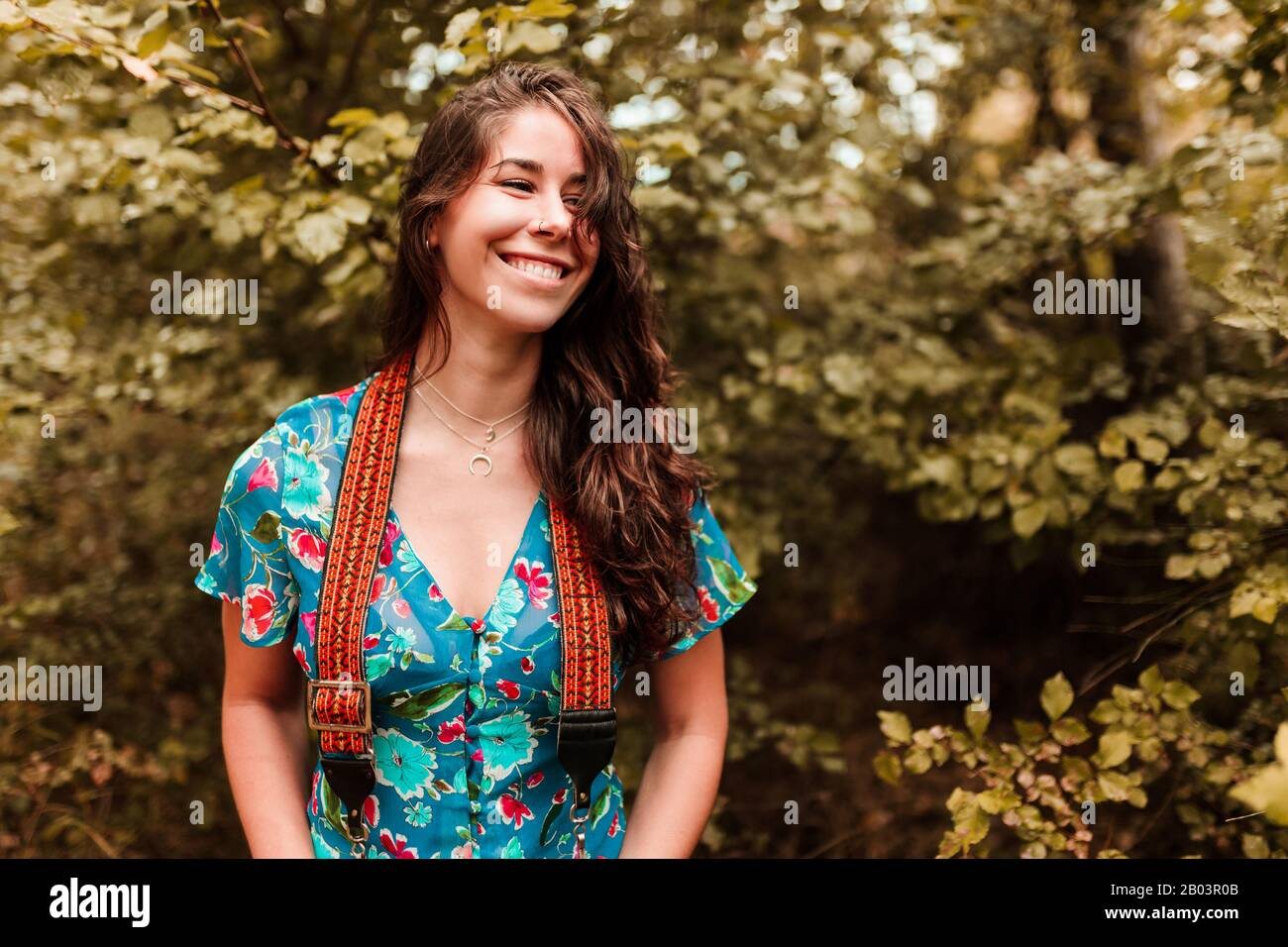 Young woman with analog camera wearing a dress in the forest Stock Photo