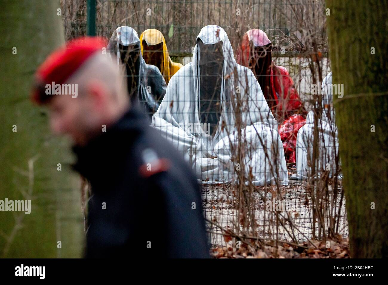 """Berlin, Germany. 04th Feb, 2020. """"The Guardians of Time"""" by the Austrian artist Manfred Kielnhofer are standing in the Tiergarten on a fenced area, which a man passes by. Credit: Christoph Soeder/dpa/Alamy Live News Stock Photo"""