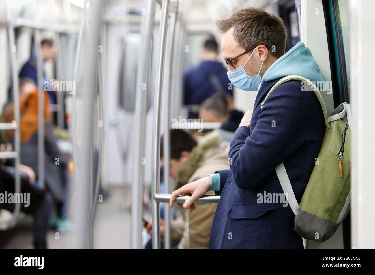 Ill man in eyeglasses feeling sick, wearing protective mask against transmissible infectious diseases and as protection against coronavirus, covid-19 Stock Photo