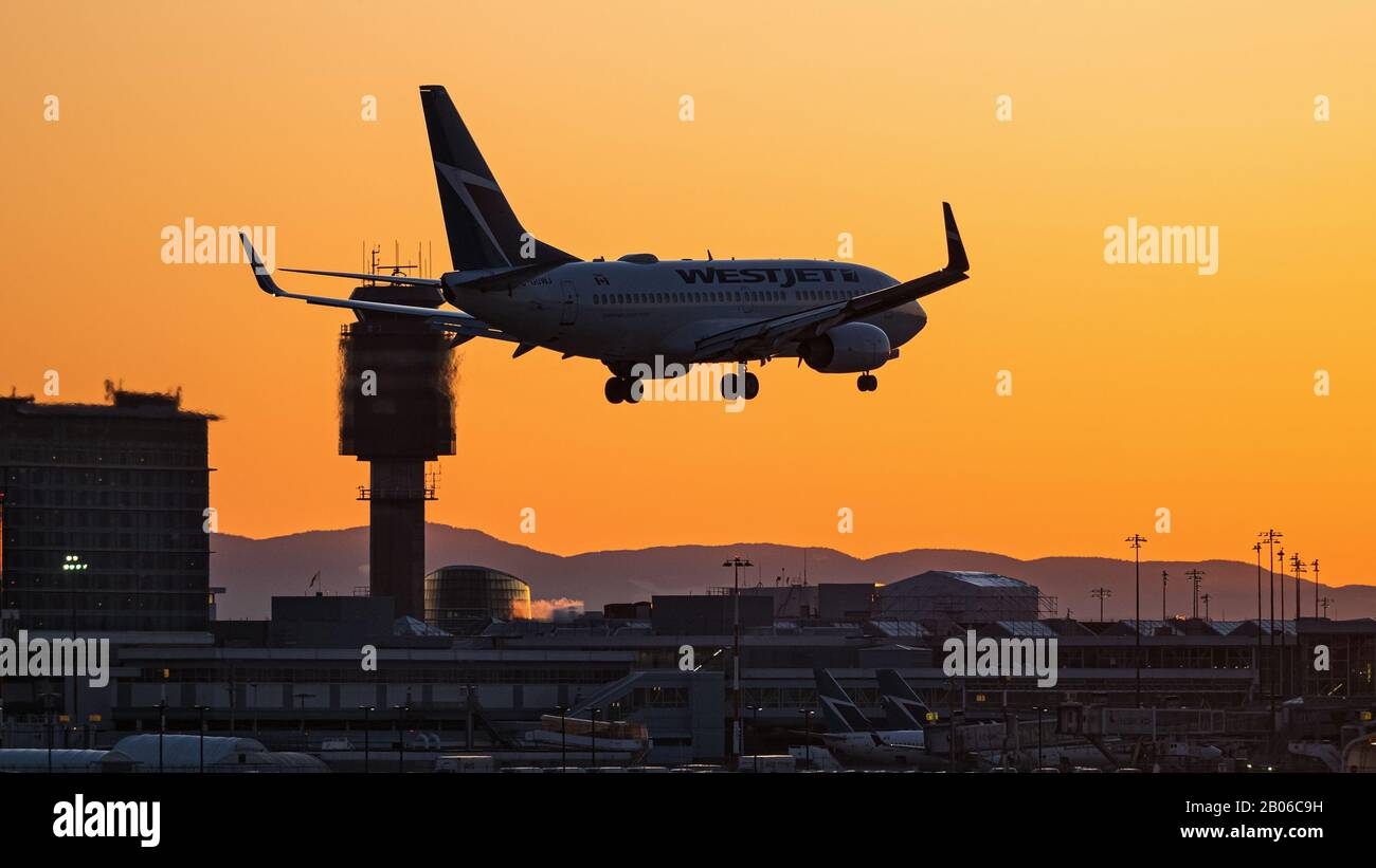 Richmond, British Columbia, Canada. 18th Feb, 2020. A Boeing 737-700 jet, belonging to WestJet Airlines (C-GUWJ), lands at sunset, Vancouver International Airport. Credit: Bayne Stanley/ZUMA Wire/Alamy Live News Stock Photo