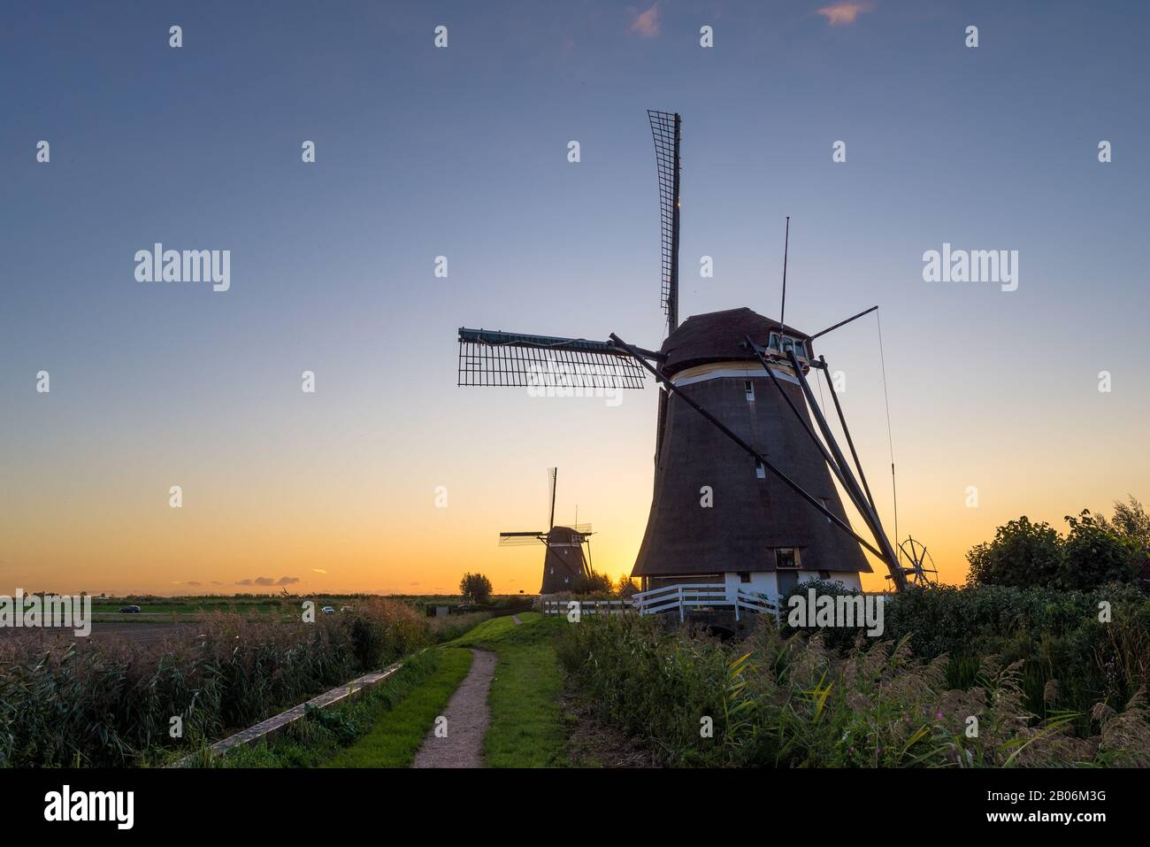 Traditional dutch windmills in a row with beautiful evening sky Stock Photo