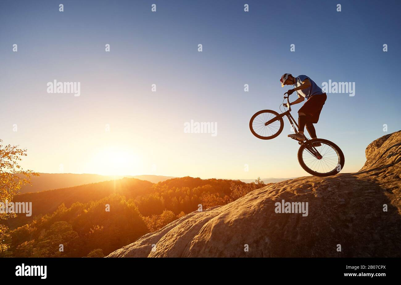 Silhouette of cyclist balancing on back wheel on trial bicycle. Courageous sportsman biker making acrobatic trick on top of rocky mountain at sunset. Concept of extreme sport active lifestyle Stock Photo