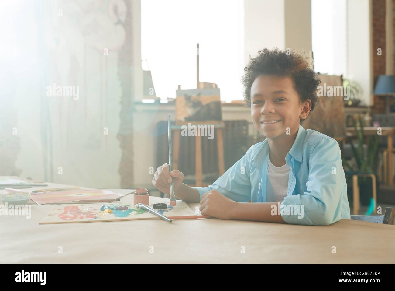 Portrait of African young boy smiling at camera while sitting at the table and drawing a picture with paints and brush Stock Photo