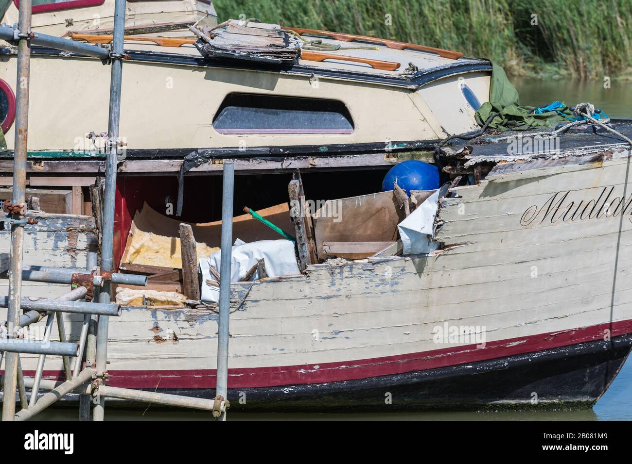 Neglected damaged wooden boat with panels missing, in need or maintenance and repair. Stock Photo