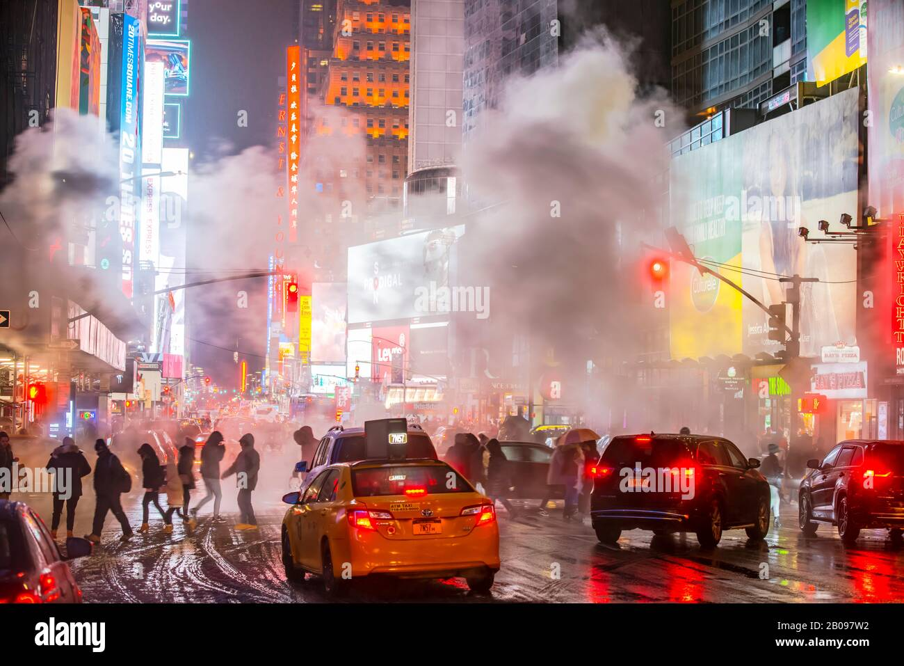 The drifting steam surrounds people, traffic and Times Square buildings in the snowy night at Midtown Manhattan New York City NY USA on Jan. 18 2020 Stock Photo