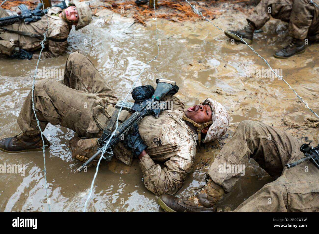U.S. Marine Corps recruits with Delta Company, 1st Recruit Training Battalion maneuver through mud and barbed wire during the Combat Endurance Course December 21, 2019 at Marine Corps Recruit Depot Parris Island, South Carolina. Stock Photo