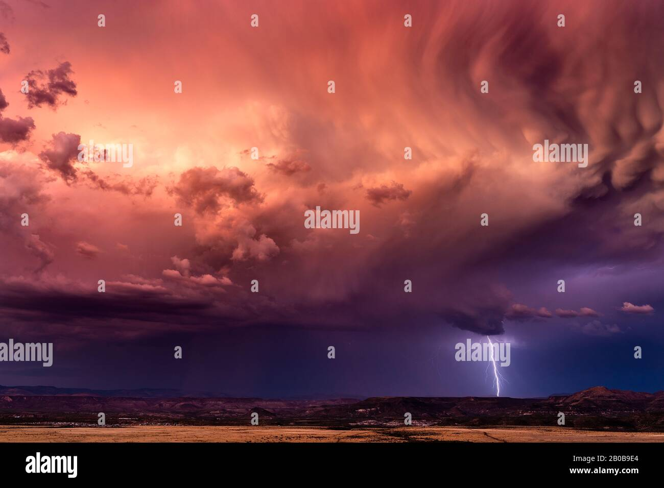 Stormy sky with dramatic clouds and lightning at sunset. Stock Photo