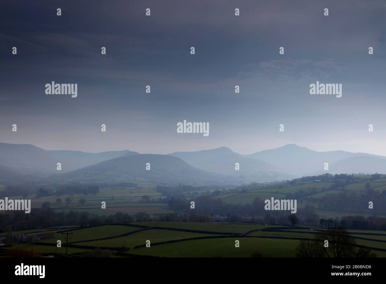 Hazy view across the Usk Valley to the peaks of Fan y Big, Cribyn and Pen y Fan in the Brecon Beacons, Wales, UK Stock Photo