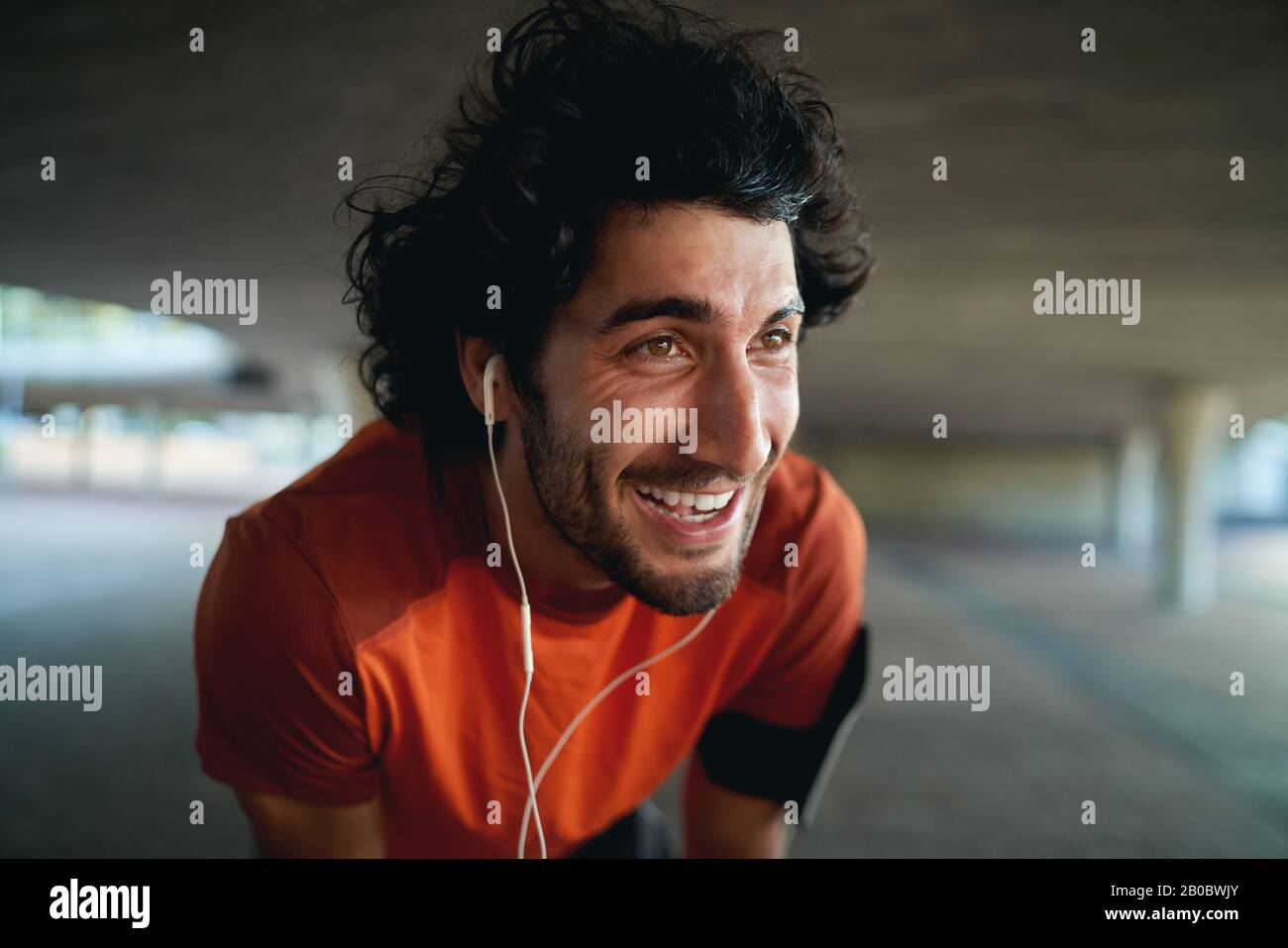 Close-up portrait of a exhausted fit young happy man with earphone in his ears taking break after jogging in the park - new year resolutions Stock Photo