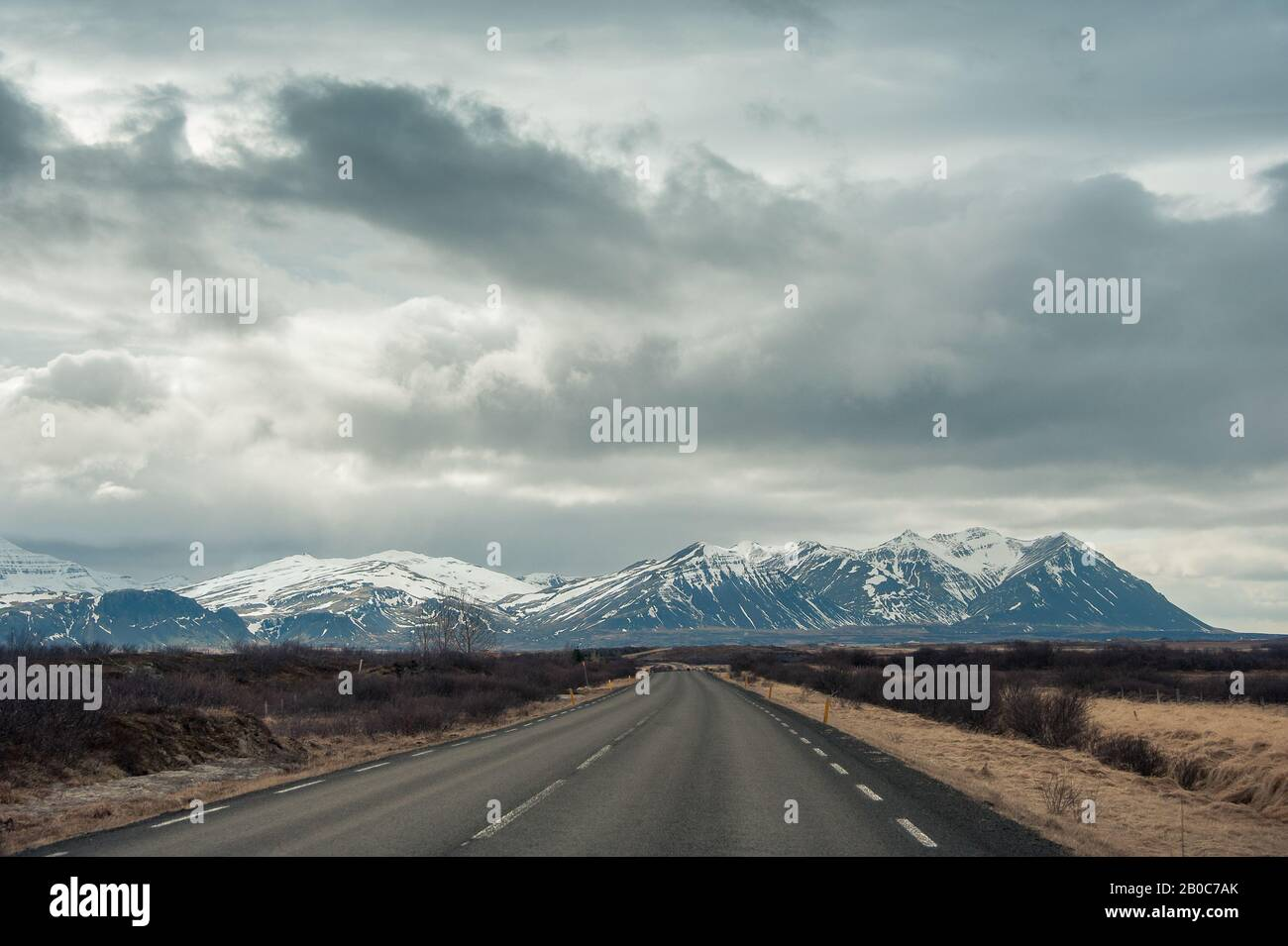 Empty road leads toward a snow capped mountain with moody, cloud sky. Stock Photo