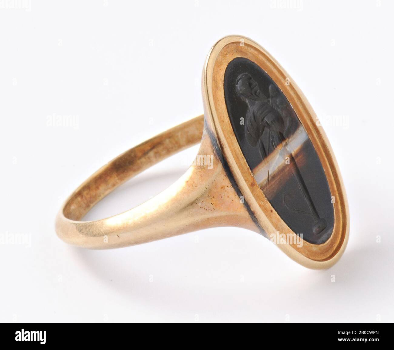 Vz: the herm is bald and has a long beard, a nebris seems to be draped over his right shoulder, the herm bears a thyrsos and at the base a pedal is shown, the herm is ithyphallisch., Gem, intaglio , ring stone, striped agate, Color: brown black Stock Photo