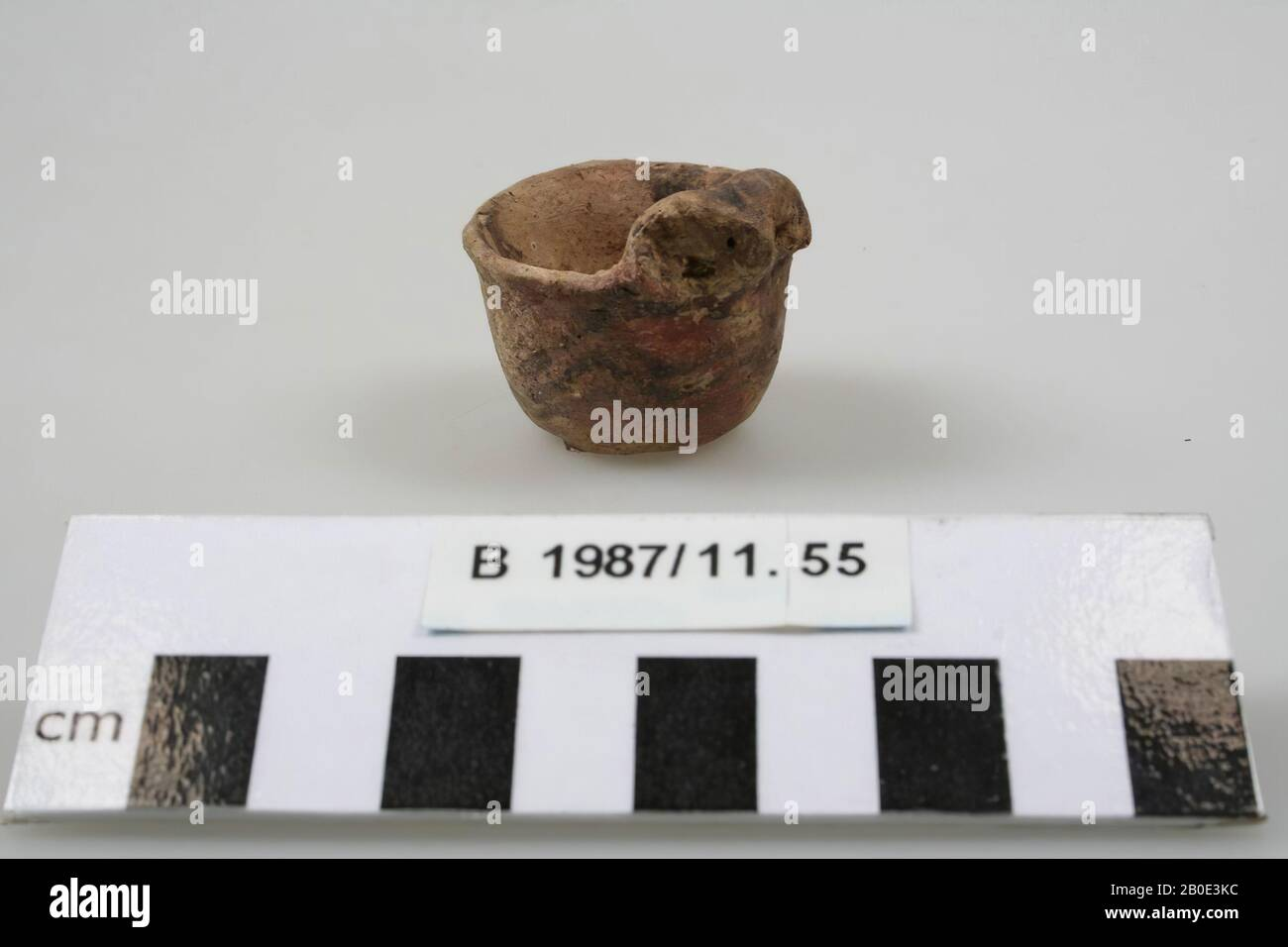 An earthenware miniature bowl with flat bottom. The wall rises steeply and bulges out slightly. The edge is bent outwards and unthickened. On the edge there is a small modeled animal head with a rounded down horn on either side. The ears are indicated by a round hole. The outside has a beige-green coating with a dark brown paint. A double horizontal line is placed under the edge and three horizontal zigzag lines on the belly. On the top and horns of the animal head we see cross stripes. The interior has a beige coating, crockery, earthenware, handmade, H 3.3 cm, D 3.3 cm, Bronze Age 1800-1150 Stock Photo