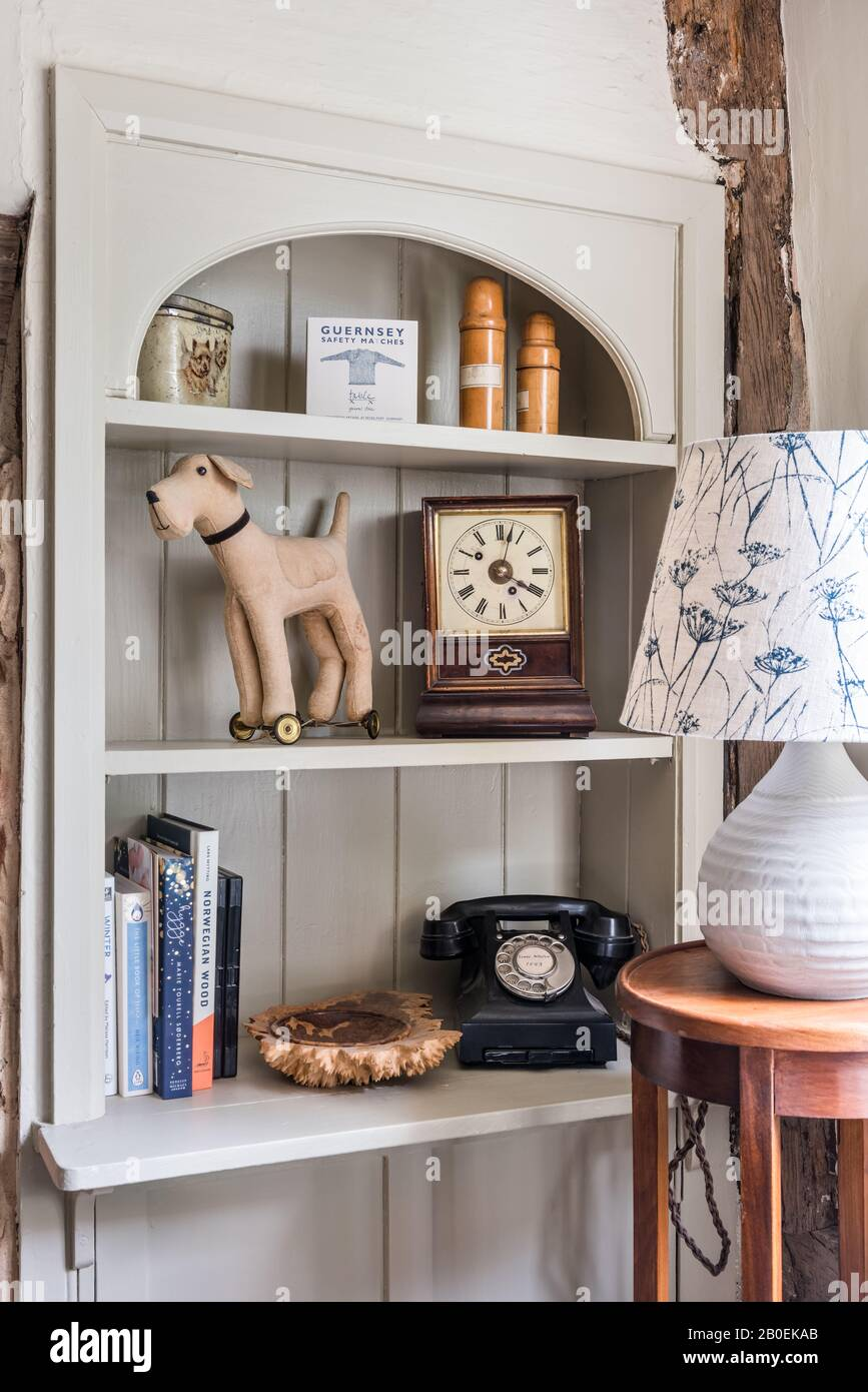 Tongue-and-groove shelving with antique clock. vintage phone and dog on wheels. Stock Photo