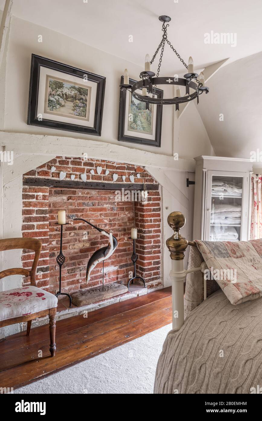 Red-brick fireplace with antique chair upholstered in Kate Forman's Red Roses. Stock Photo