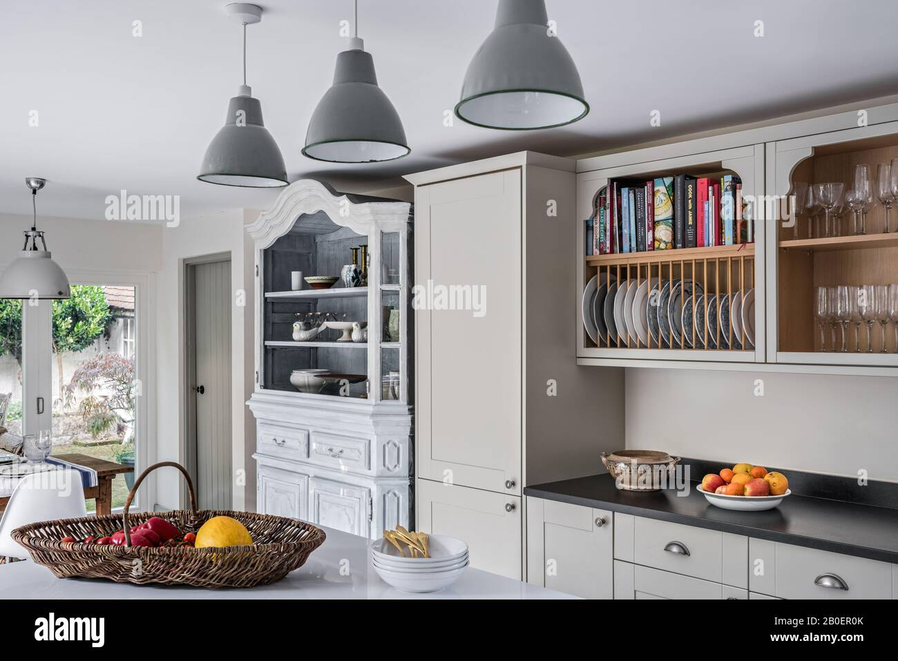 Belgian oak armoire, dating from the 1940's with painted factory lampshades from Amiens in Quaker style kitchen with plate rack above granite worktop. Stock Photo