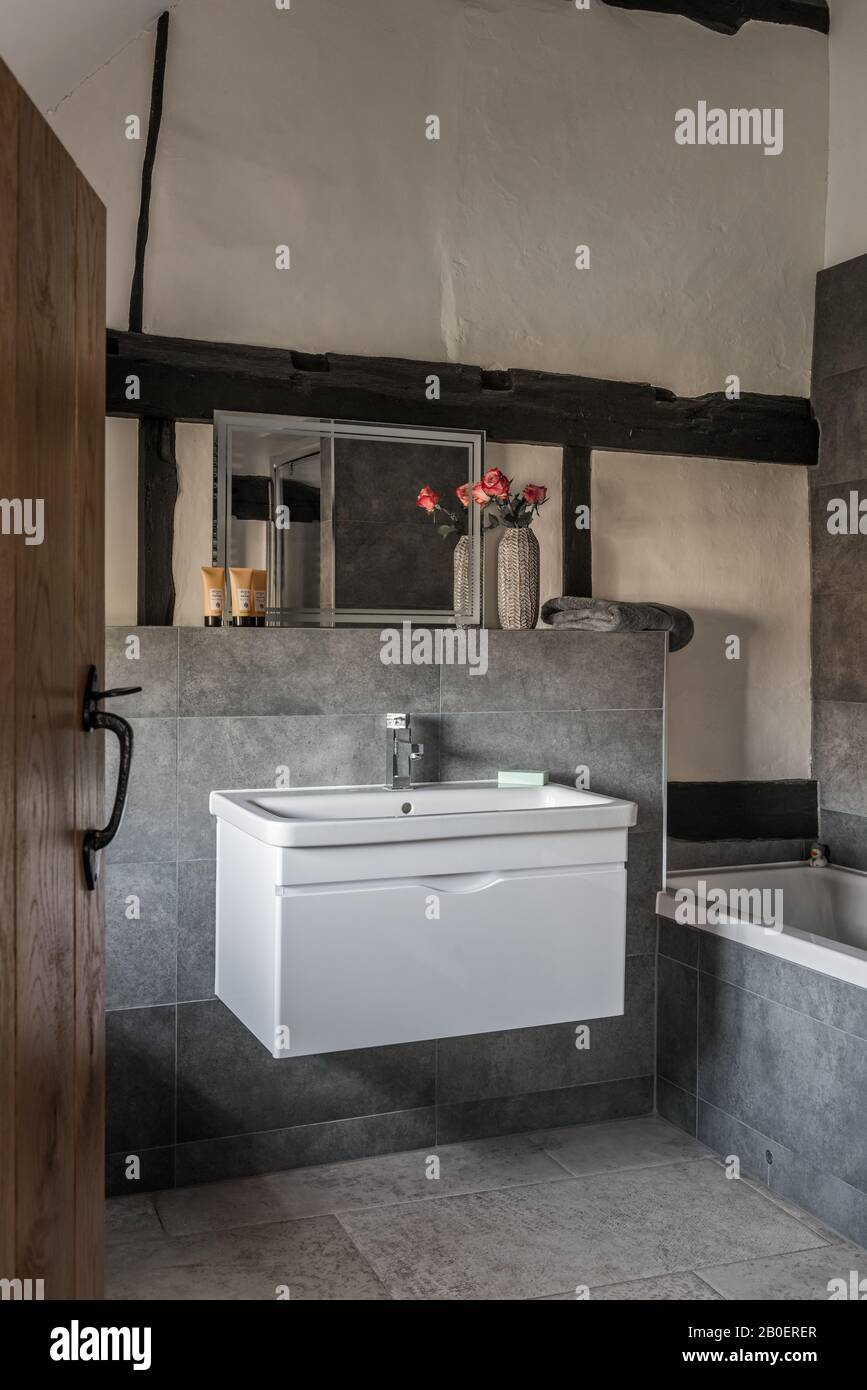 Uneven plastered walls contrasted by clean lines of contemporary basin unit. Stock Photo