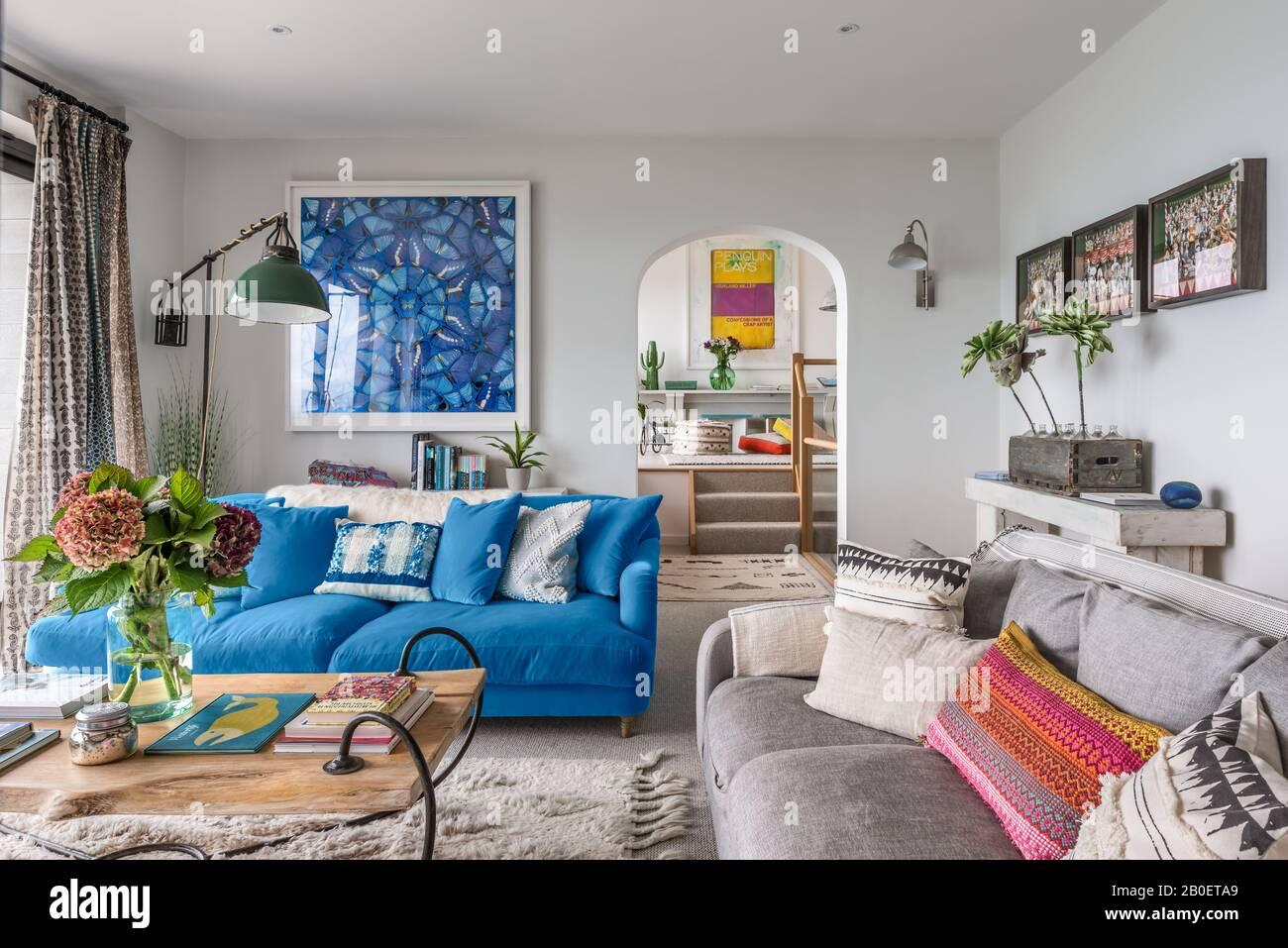 Damien Hirst artwork with Indian fabric panels and arch leading to open-plan kitchen-diner Stock Photo