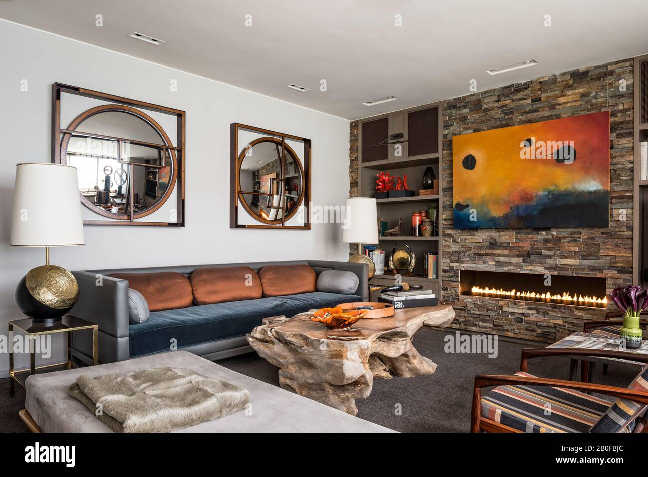 Slate lined wall with coffee table made from a solid piece of wood, antique lamps, and mirrors by Holly Hunt. Stock Photo