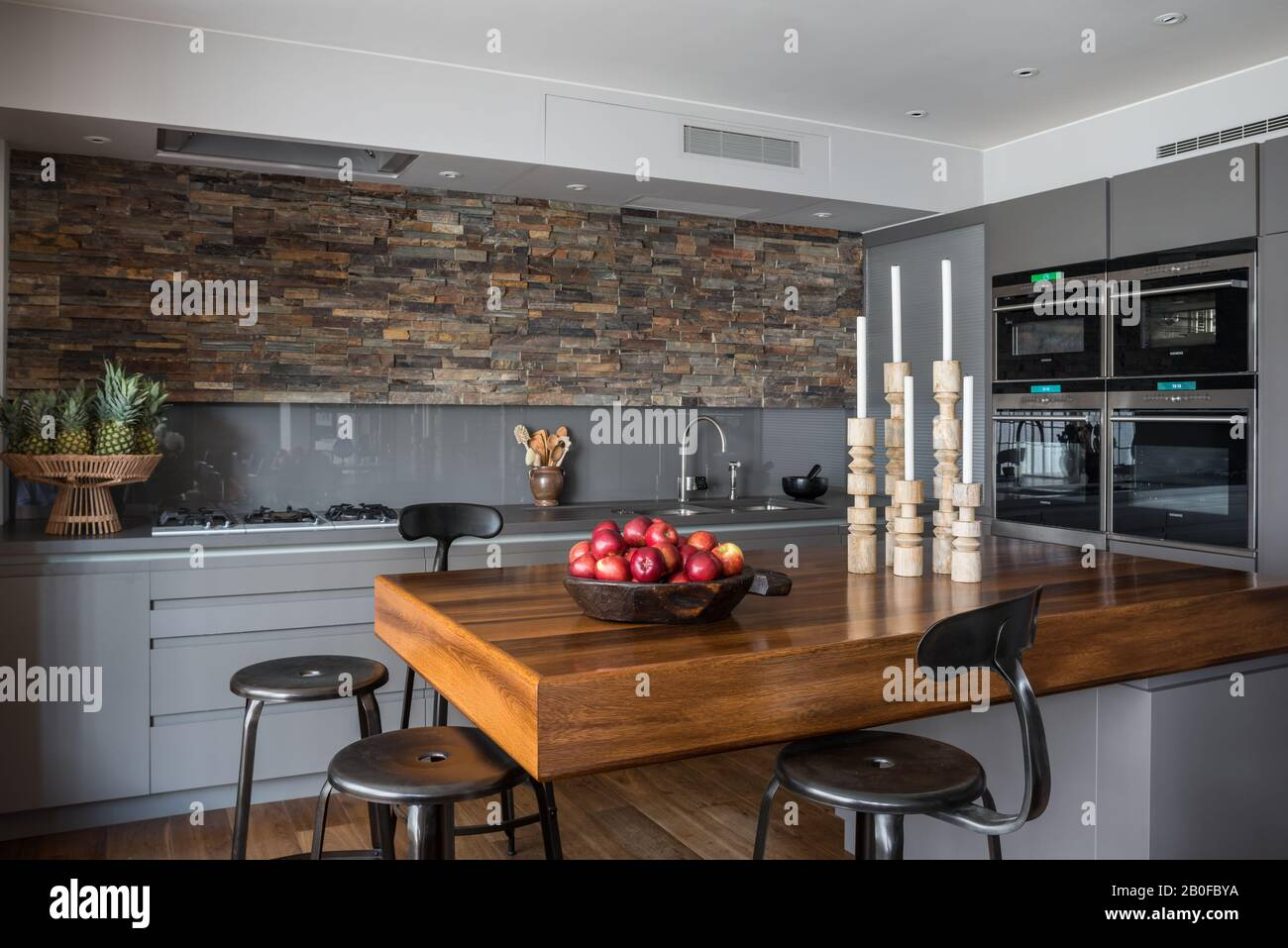 Teak breakfast bar with slate lined walls in kitchen of modern West London apartment. Stock Photo