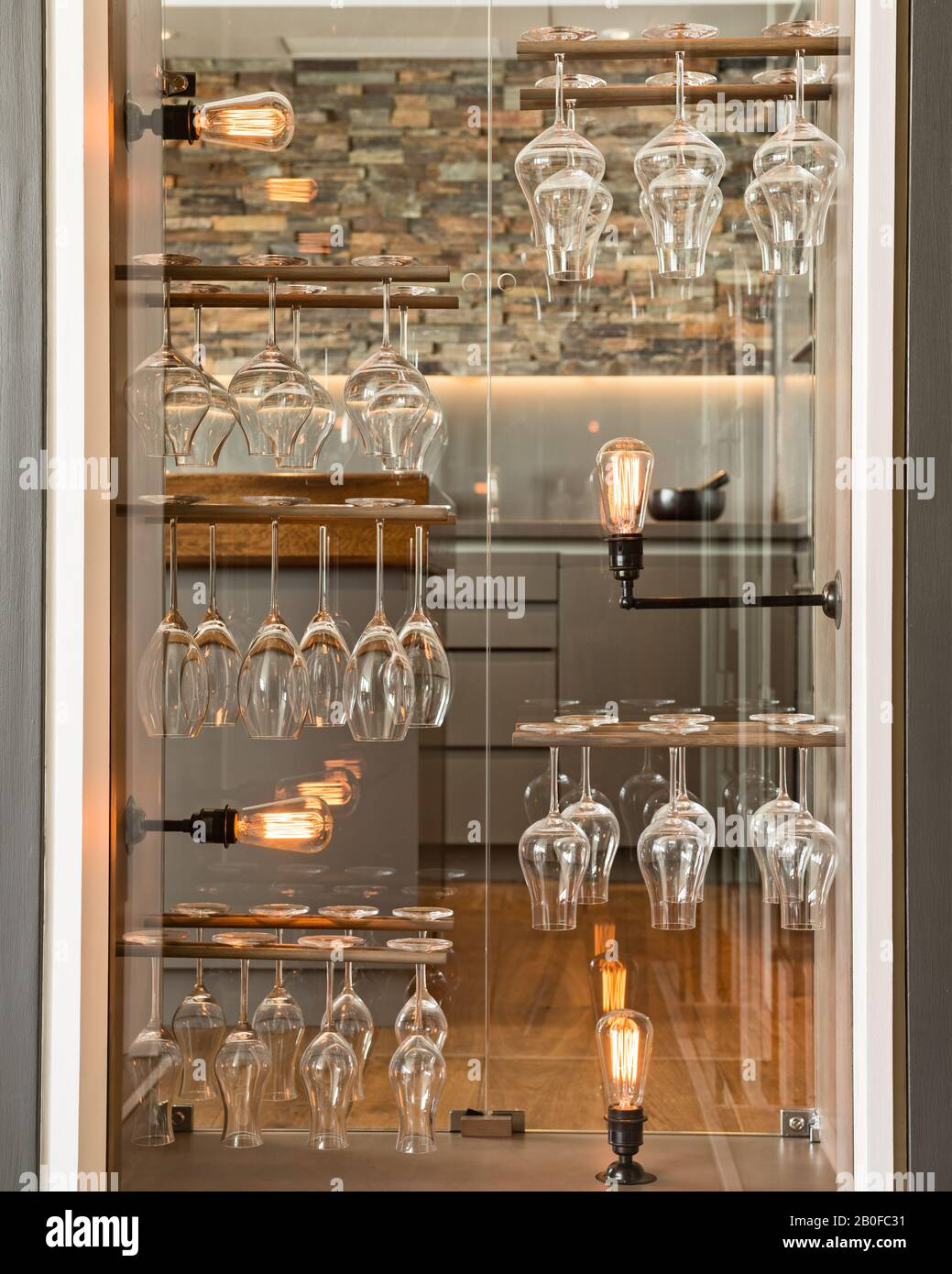 Redel wineglass storage with filament bulbs in repurposed doorway cabinet. Stock Photo