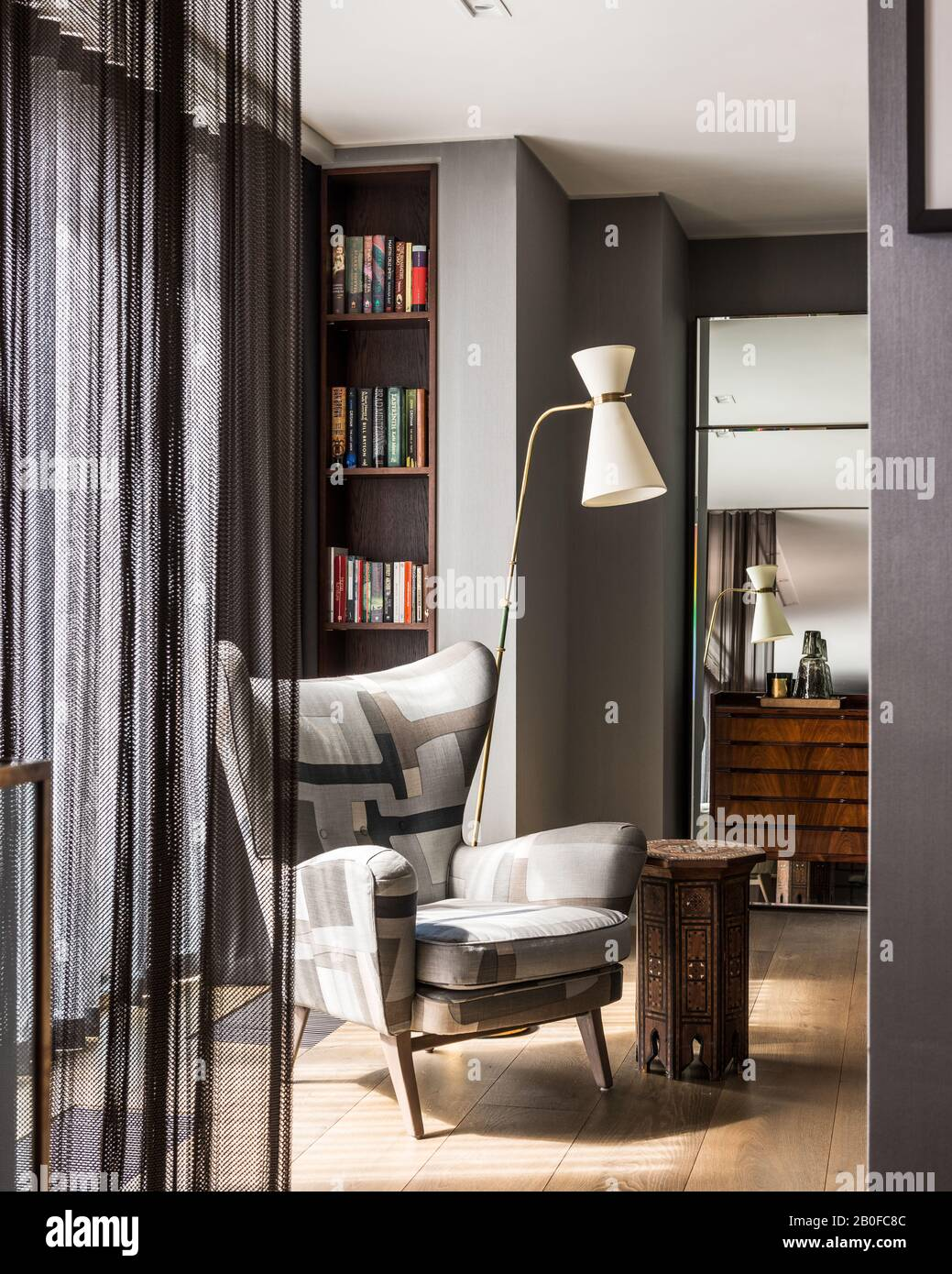 Diablo Modernist floor lamp and upholstered chair in bedroom of West London apartment Stock Photo