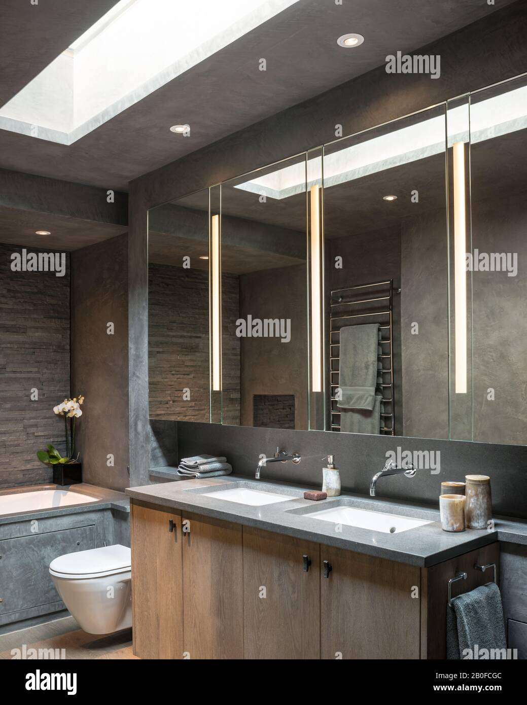 Large mirrored cabinets with double basins below skylight in modern West London apartment. Stock Photo