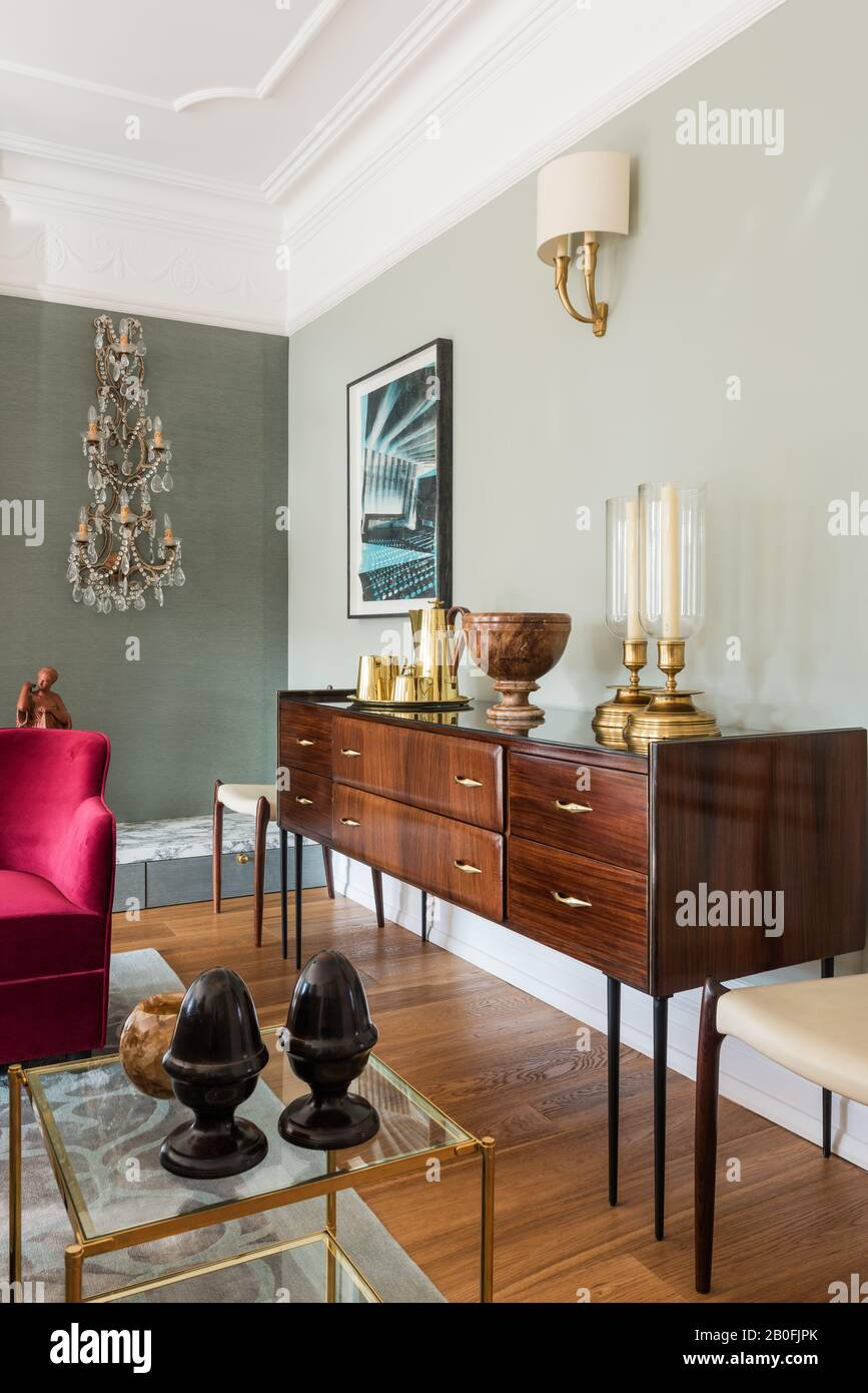 Blend of vintage and contemporary pieces, Yoko sideboard and bespoke armchair in red velvet Stock Photo
