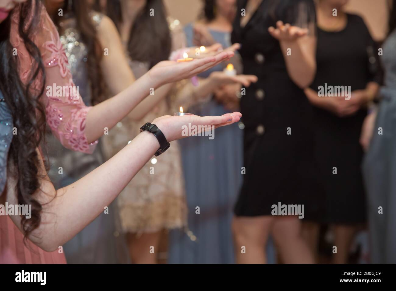 Holding hands on henna candle . She holds the candle in his hand Henna party . Stock Photo