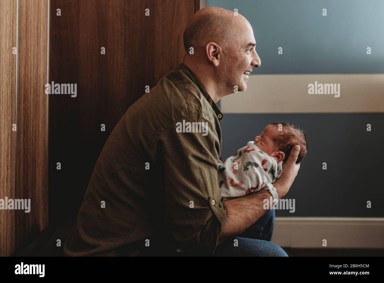Side view of happy father holding newborn son in hospital Stock Photo