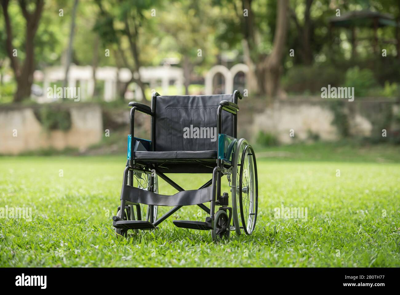 Empty wheelchair parked in park, Health care concept. Stock Photo