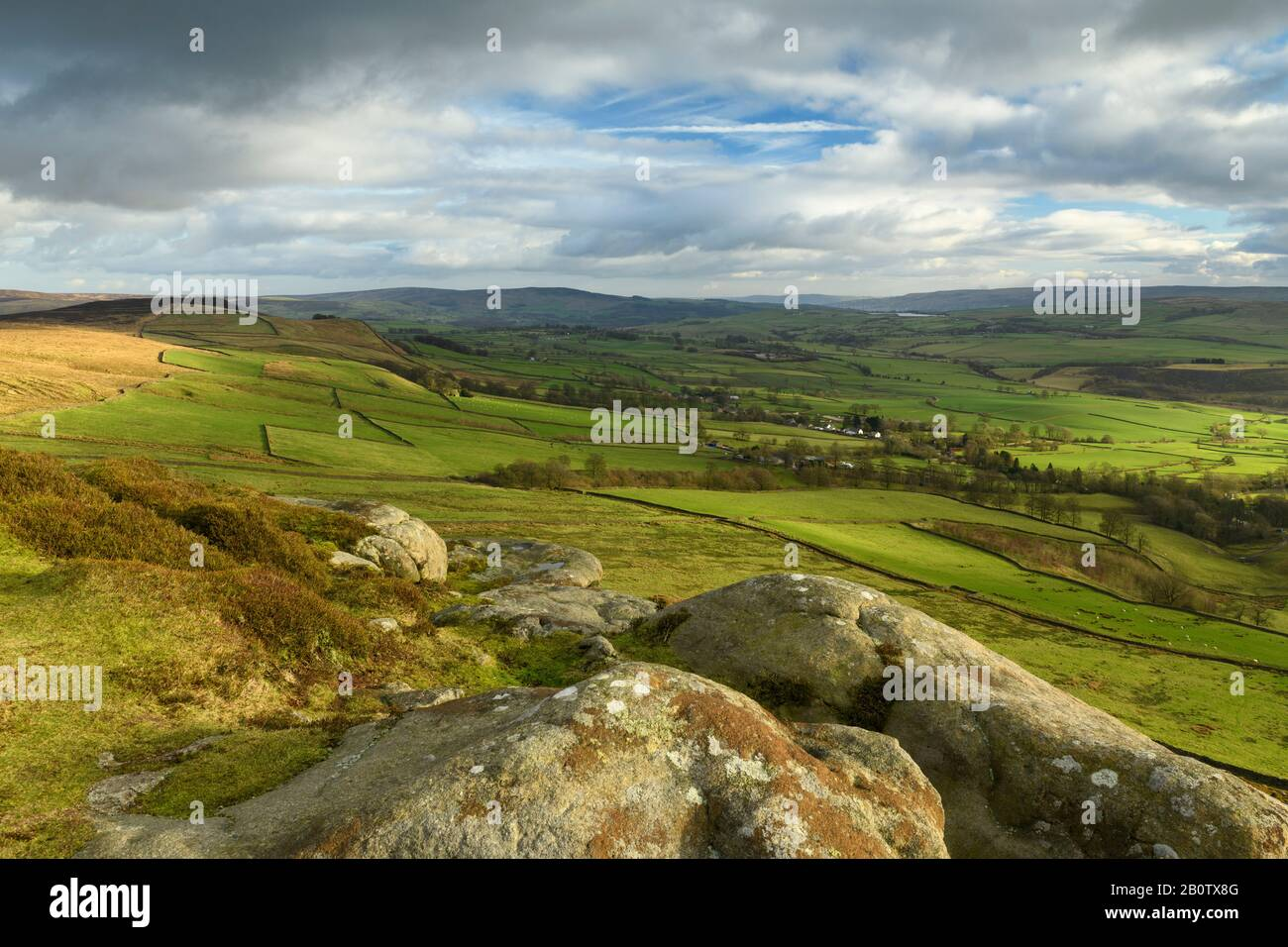 Scenic rural view from Embsay Crag (sunlit fells or moors, farm fields in valley, high upland hills, dramatic sky) - North Yorkshire, England, UK. Stock Photo