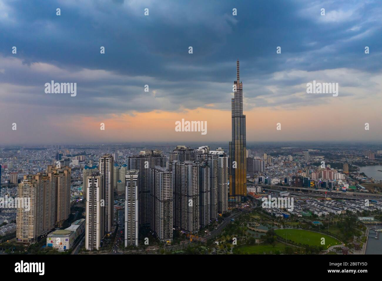 Dramatic aerial view of Landmark Building and Ho Chi Minh City skyline at sunset with beautiful stormy and dark clouds in the sky Stock Photo