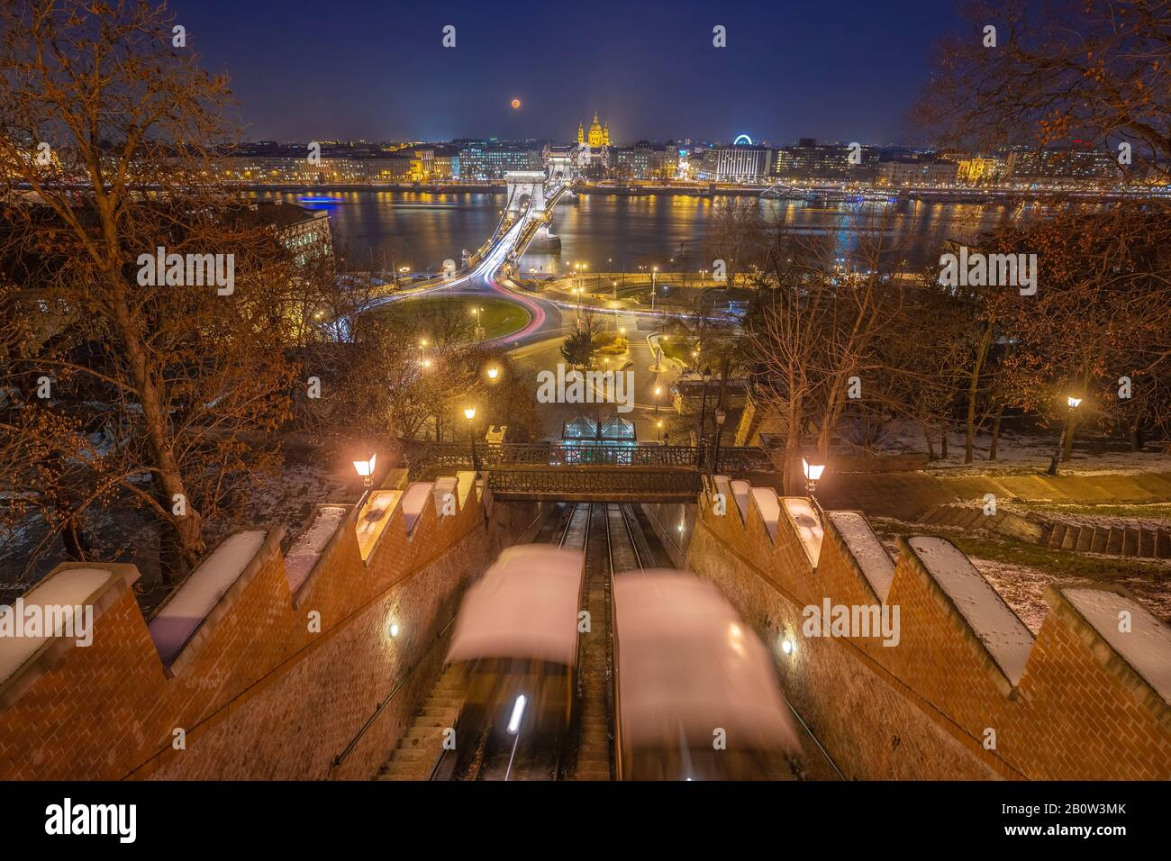 Budapest, Hungary - View from the Buda Castle Hill at blue hour with moving funiculars, Szechenyi Chain Bridge, St. Stephen's Basilica and blood Moon Stock Photo