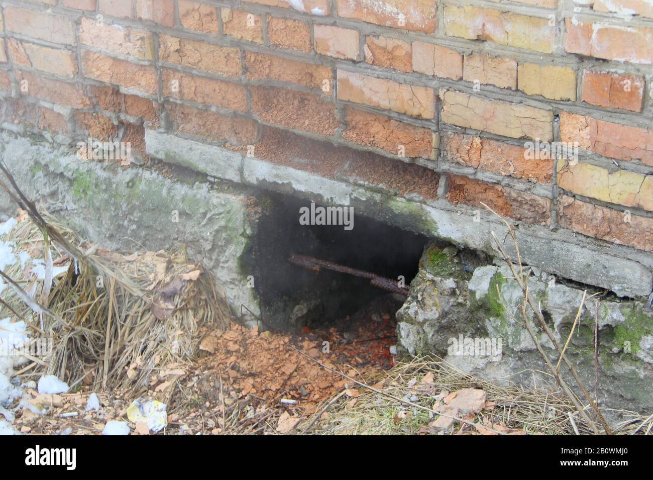 Hole In A Brick Wall Of A House The Foundation Of The House Covered With Moss Construction Waste Pieces Of Rubble Stock Photowith Empty Space For Text And Design Stock Photo