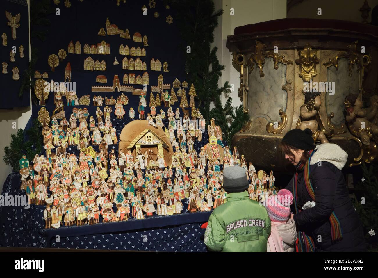 Young visitors observe the traditional gingerbread nativity scene (perníkový betlém) displayed in Saint Matthias Church (Kostel svatého Matěje) in Dejvice district in Prague, Czech Republic. Gingerbread figures of the nativity scene are baked annually in the church in the Christmas season. Stock Photo