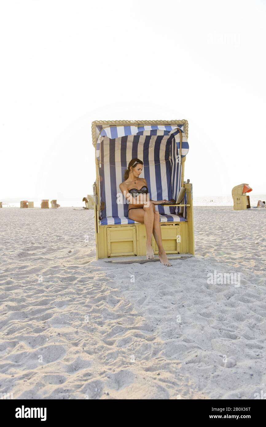 Young woman with laptop on the beach, Niendorf on the Baltic Sea, Schleswig-Holstein, Germany, Stock Photo