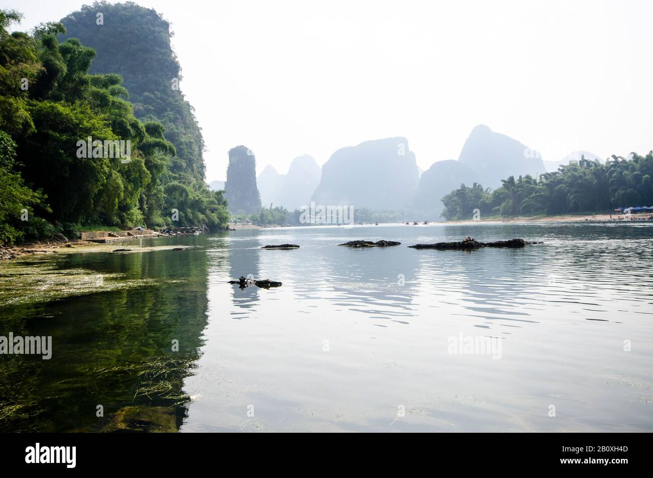 A view along the banks of the Li River, Yangshuo, Guilin, China. With bamboo forests on either side and distant mountains fading into the mist. Stock Photo
